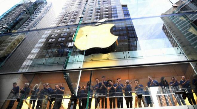 El personal de una tienda Apple observa a varias personas que hacen...