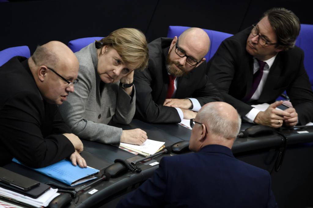 El ministro alemán de la Cancillería, Peter Altmaier, la canciller alemana, Angela Merkel, el secretario general del partido Unión Cristianodemócrata (CDU), Peter Tauber, el jefe del grupo parlamentario conservador, Volker Kauder, y el secretario general de la Unión Socialcristiana (CSU), Anderas Scheuer, hablan durante la la sesión constituyente del nuevo Parlamento alemán, en Berlín, Alemania, el 24 de octubre de 2017. El exministro de Finanzas Wolfgang Schäuble estará a partir de ahora al frente del hemiciclo, mientras avanzan las negociaciones para formar un gobierno tripartito entre conservadores, liberales y verdes liderado por Ángela Merkel.