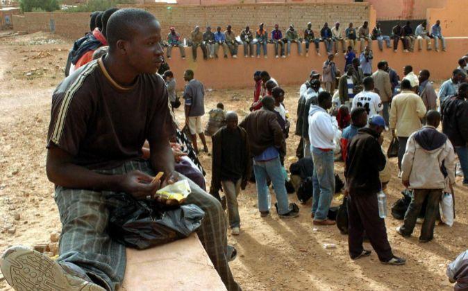 Foto de archivo.  Un grupo de inmigrantes subsaharianos comen los...