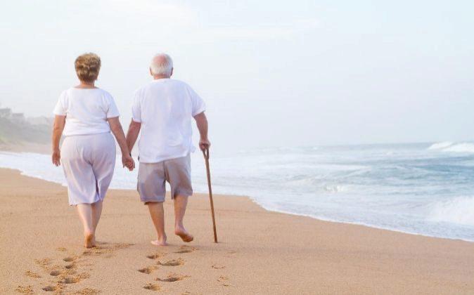 Una pareja de jubilados pasean junto al mar.