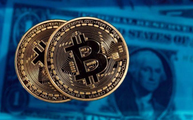 Imagen de bitcoins con billetes de dólares de fondo