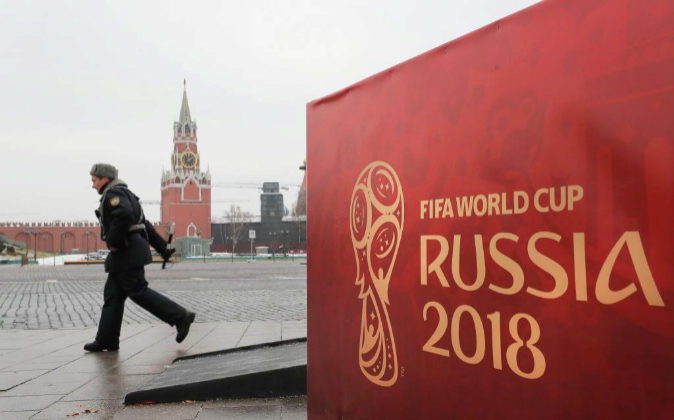 Un oficial del Ministerio de Interior ruso pasa junto a un cartel de...
