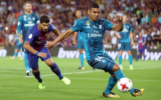 Casemiro disputa un balón con Luis Suárez.