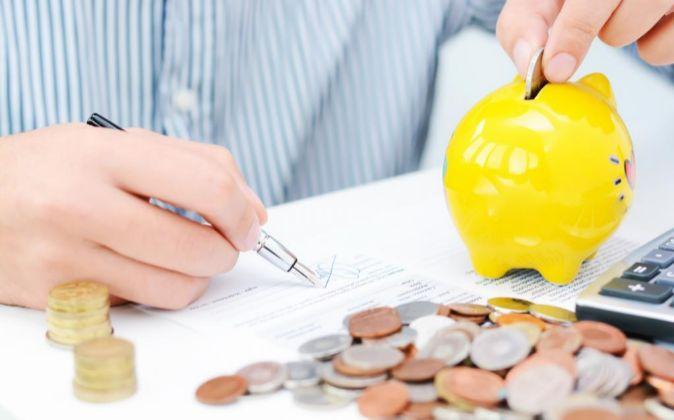 Un hombre hace cálculo con una hucha y dinero.
