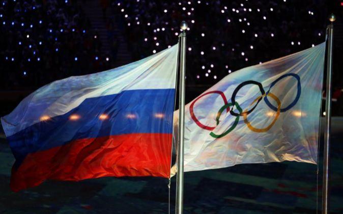 La bandera Olímpica y la rusa (i), ondean durante los Juegos...