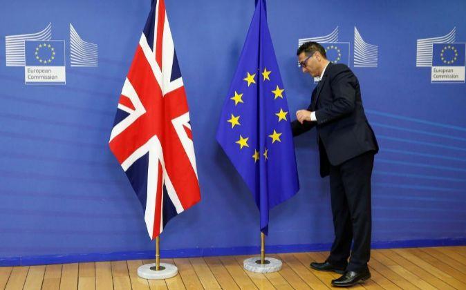Un trabajador de la Comisión Europea (CE) coloca la bandera...