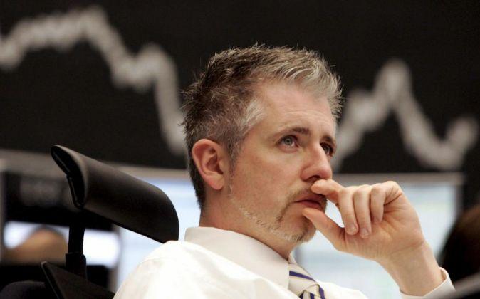 Bróker preocupado mirando una pantalla con el comportamiento de la...