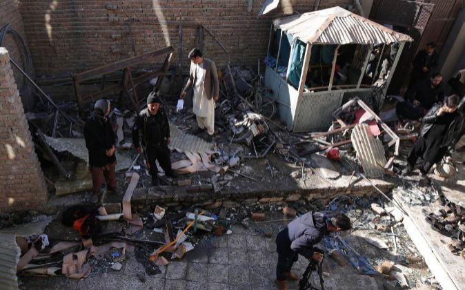 Oficiales de seguridad afganos inspeccionan los daños en el escenario...