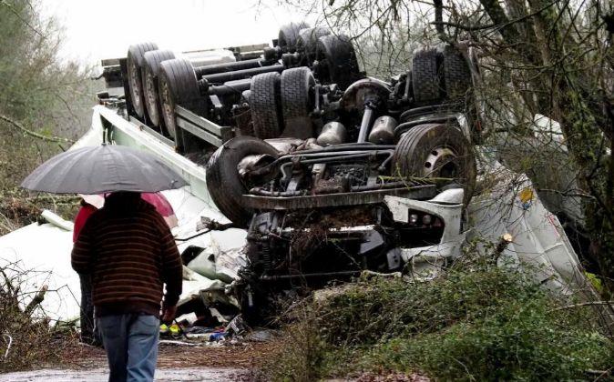 Varias personas observan el estado en el que quedó un camión...
