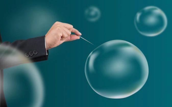 Recreación de un ejecutivo pinchando una burbuja