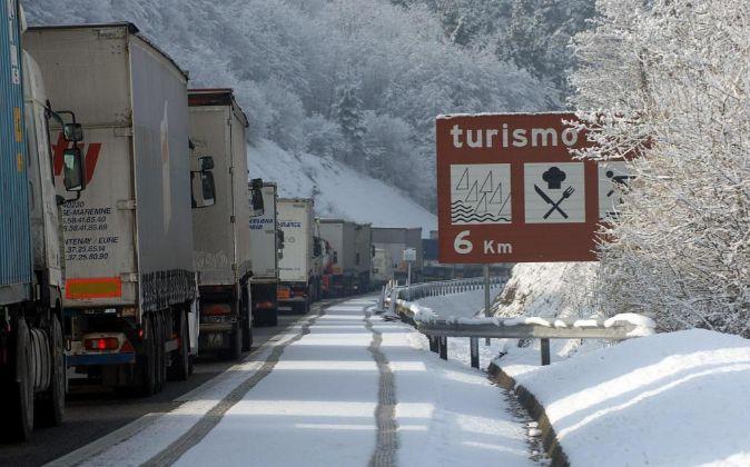 Foto de archivo de camiones atrapados por la nieve a su paso por...