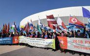 Surcoreanos ondean banderas internacionales, incluida la norcoreana,...