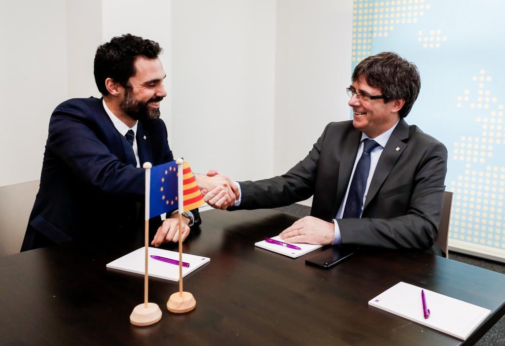 El expresidente de la Generalitat Carles Puigdemont (d) estrecha la...