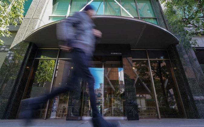 Un corredor sobrepasa la fachada de Coincheck Inc. en Tokio el pasado...