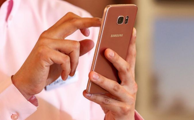Un empleado de Samsung Electronics con un smartphone de la tienda en...