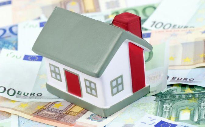 Maqueta de una vivienda sobre billetes de euro