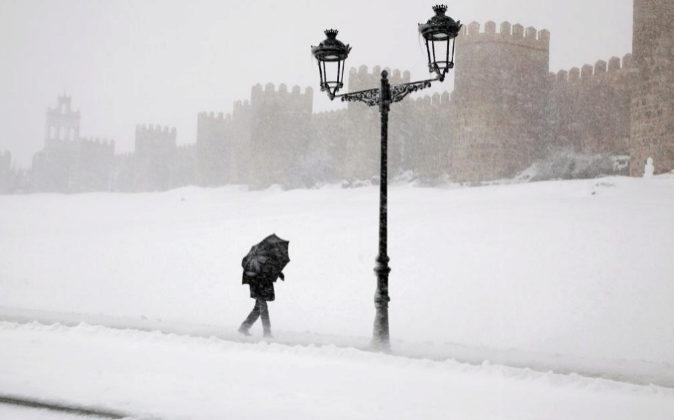 Un hombre se protege ayer con un paraguas de la ventisca y la nieve en...