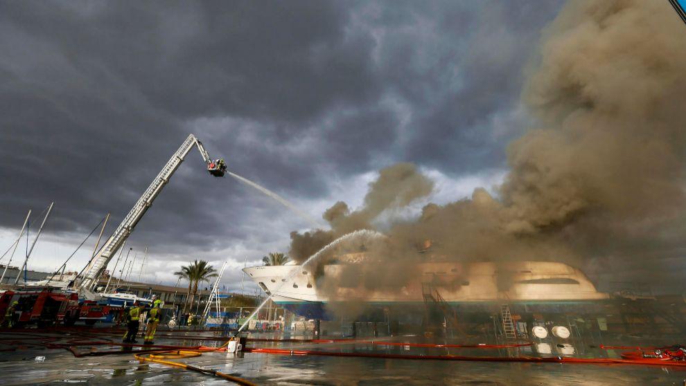 Los bomberos de Alicante apagando el fuego en el yate de Alicante.