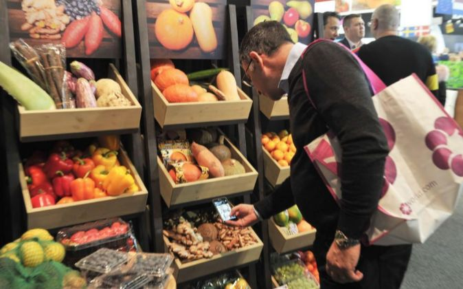 Un visitante de la Feria Fruit Logistica 2018 observa un expositor de...