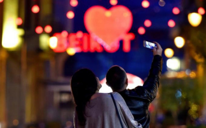 Una pareja posa en una calle decorada con motivo de la celebración de...