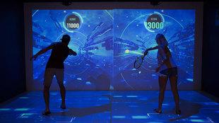 Dos visitantes juegan en el simulador del Rafa Nadal Museum Xperience,...