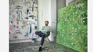 El artista, 37 años, sentado entre dos de sus obras. A la izqda.,...