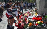 Turistas ponen flores por el atentado en las Ramblas de Barcelona.