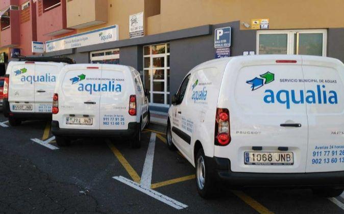 Vehículos de Aqualia aparcados junto a una oficina de la filial de...