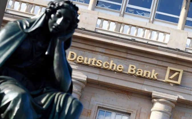 A statue sits outside a branch of Deutsche Bank AG in Frankfurt,...