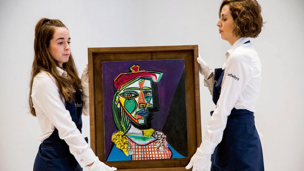Dos trabajadoras de Sotheby's trasladan la obra Mujer con boina y...