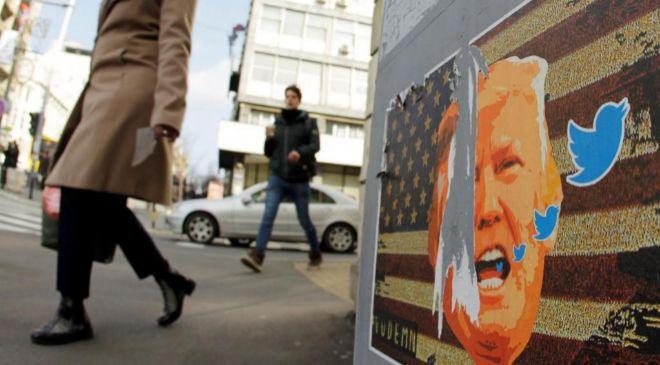 Una mujer pasa por delante de un cartel de Trump con logos de la red...
