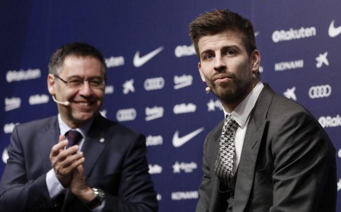 El central del FC Barcelona Gerard Piqué posa con el presidente del...