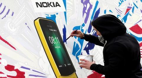 Un artista pinta un cartel del nuevo Nokia 8110 en el Congreso Mundial...