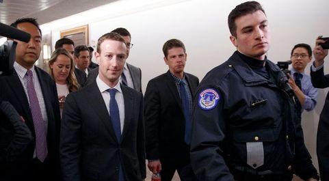 El director ejecutivo de Facebook Mark Zuckerberg (c) camina a la...