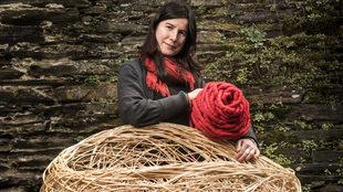 La cestera Idoia Cuesta, 49 años, sostiene un adorno de mimbre...