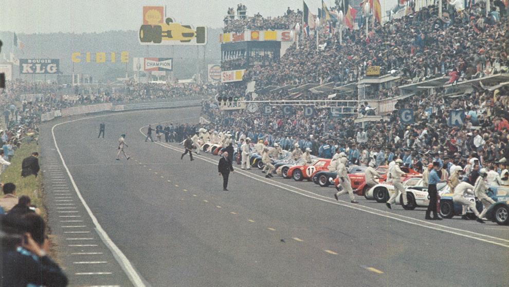 El piloto belga Jacky Ickx, en mitad de la pista, se dirige con...