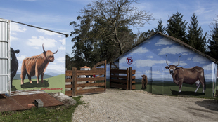 Entrada al establo de Fisterra Bovine World, con murales obra del...