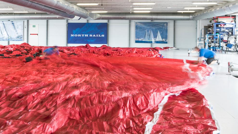 Dos trabajadores de North Sails extienden uno de los...