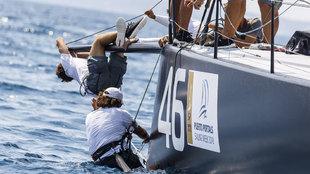 Dos tripulantes del barco Luna Rossa intentado reparar la embarcación...