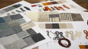 Sobre el tablero, muestras de tejidos de distinta tonalidad y textura.