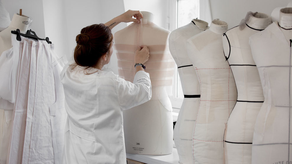 Una costurera confecciona un vestido de organza de color rosa.