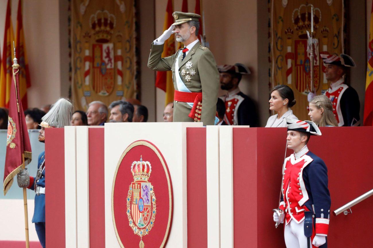 El rey Felipe saluda durante el tradicional desfile que este año ha...