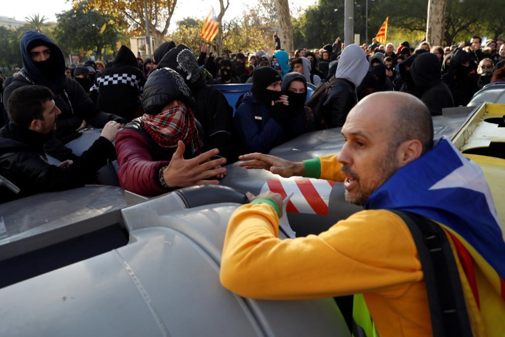 Un manifestante independentista trata de impedir que un grupo de...