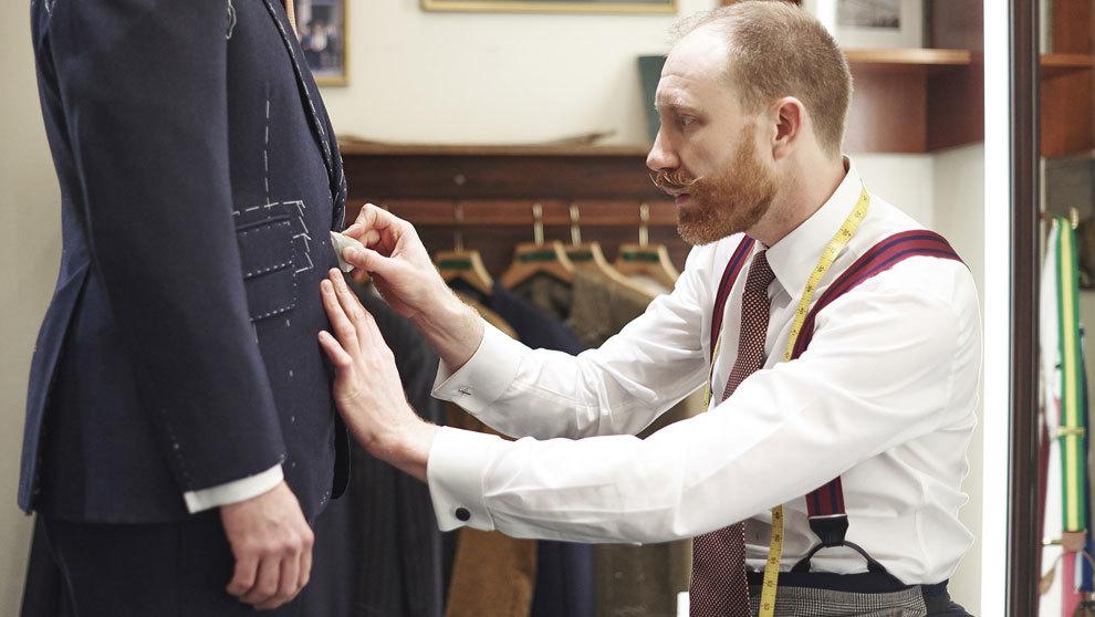 Thomas Pendry identifica el punto para colocar el botón a la chaqueta...