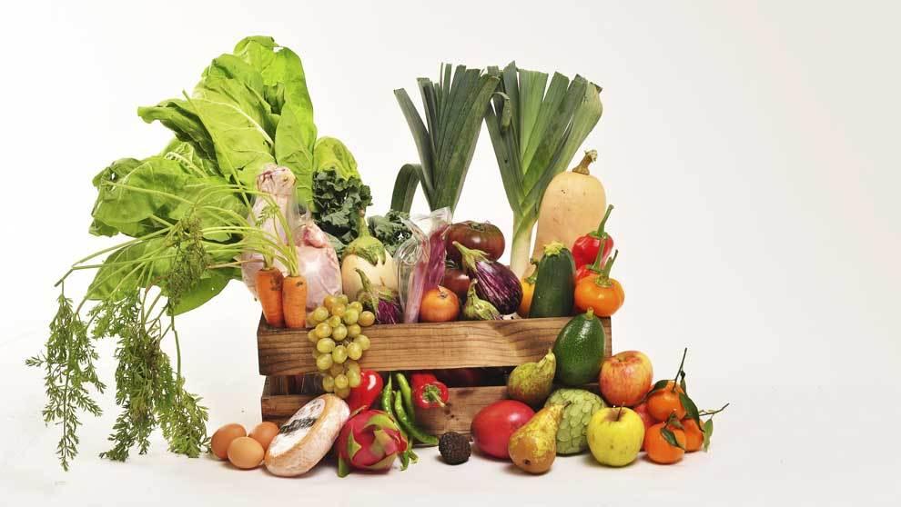 Cesta con pimientos,zanahorias, calabacín, puerros y manzana roja, de...