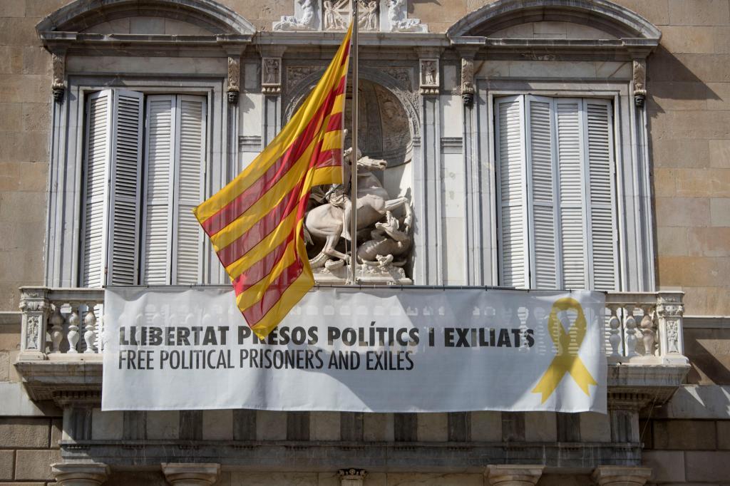 """GRAFCAT5555. BARCELONA, 12/03/2019.- Vista de la fachada del Palau de la Generalitat de donde cuelga, junto a la bandera catalana, un cartel y un lazo <HIT>amarillo</HIT> reivindicando la libertad de los políticos encarcelados, después de que ayer lunes la Junta Electoral Central diese un plazo máximo de 48 horas al presidente del Govern, Quim Torra, para que ordene la retirada de las """"esteladas"""" y <HIT>lazos</HIT><HIT>amarillos</HIT> que puedan encontrarse en los edificios públicos dependientes de la Generalitat para """"mantener la neutralidad política durante los procesos electorales"""". EFE/Marta Pérez"""