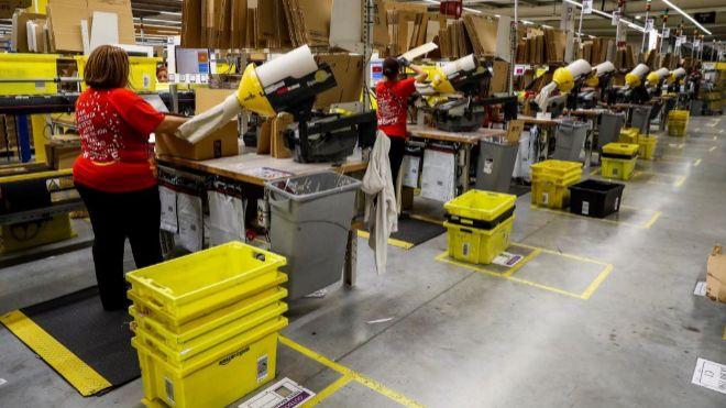 Varios operarios trabajan en la nave de distribución de Amazon en...