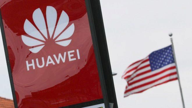Logotipo de Huawei junto a una bandera de Estados Unidos en Kuala...