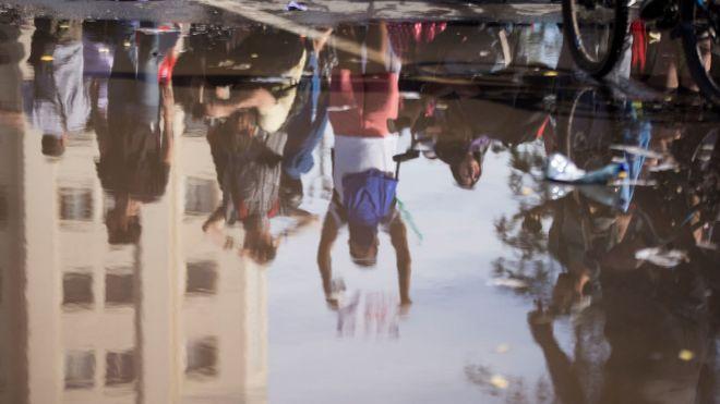 Reflejo en el agua de un grupo de manifestantes durante una nueva jornada de protestas ayer en Santiago de Chile.