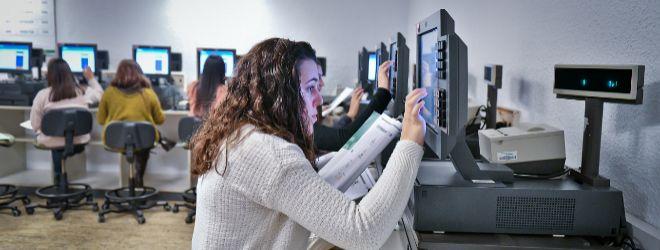 Varios empleados aprenden a utilizar una caja registradora antes de incorporarse a tienda para la campaña de Navidad.